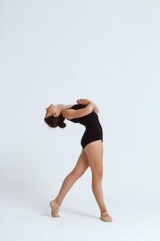 Joven hermosa bailarina contemporánea posando sobre la pared blanca. copia espacio