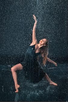 Joven hermosa bailarina moderna bailando bajo gotas de agua