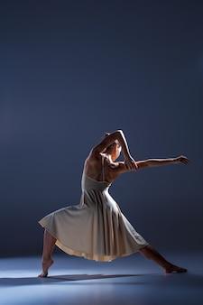 Joven hermosa bailarina en vestido beige bailando sobre fondo gris