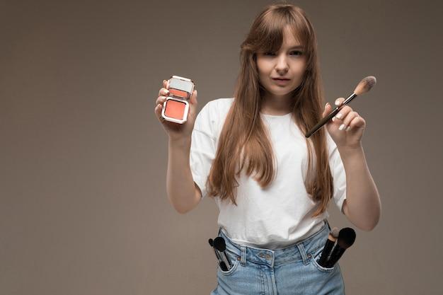 Una joven hermosa con cabello rústico largo y ondulado, maquillaje nud, en una camiseta blanca, sostiene un pincel de maquillaje y rubor, y muchos pinceles de maquillaje en los bolsillos de su ginebra