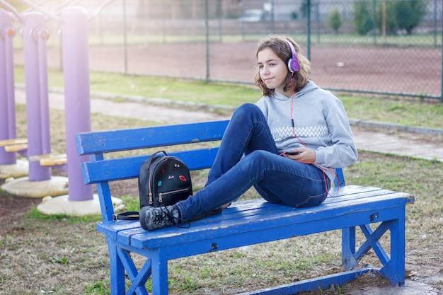 Joven hermosa chica adolescente de moda escucha música en auriculares desde un teléfono inteligente