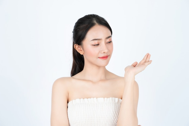 Joven hermosa chica asiática en camiseta blanca, tiene una piel sana y brillante, presentando el producto.