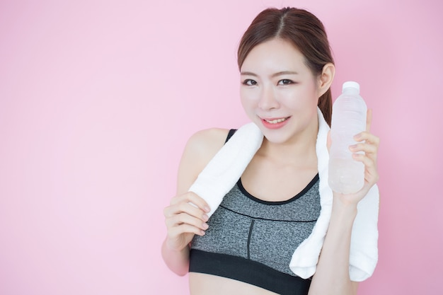 Joven hermosa chica asiática limpia piel fresca con botella de agua