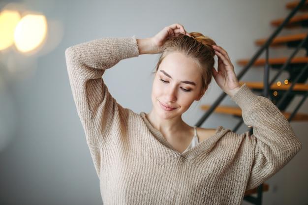 Joven hermosa chica con cabello rubio en vestido de seda beige de noche y acogedor cárdigan delante de las escaleras en casa