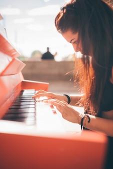 Joven hermosa chica caucásica tocando el piano