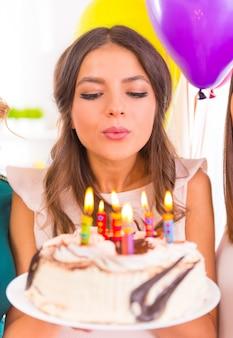 Joven hermosa chica celebrando cumpleaños en casa fiesta.