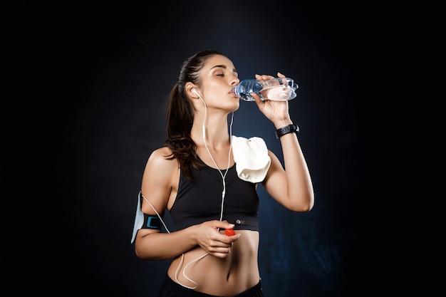 Joven hermosa chica deportiva agua potable sobre la pared oscura.