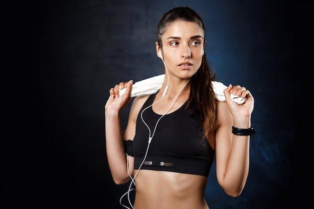 Joven hermosa chica deportiva escuchando música sobre la pared oscura.