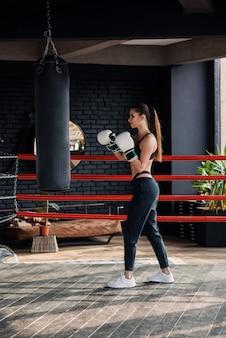 Joven hermosa chica deportiva en ropa deportiva y guantes de boxeo golpea un saco de boxeo en el moderno gimnasio negro.
