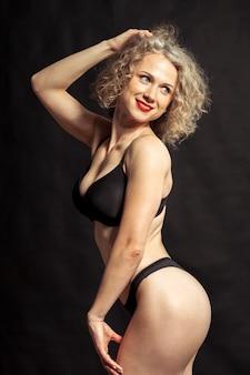 Joven hermosa chica desnuda aislada en un negro