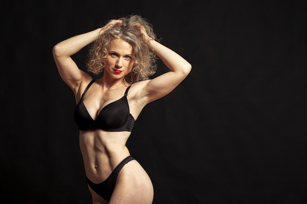 Joven hermosa chica desnuda aislada sobre un fondo negro