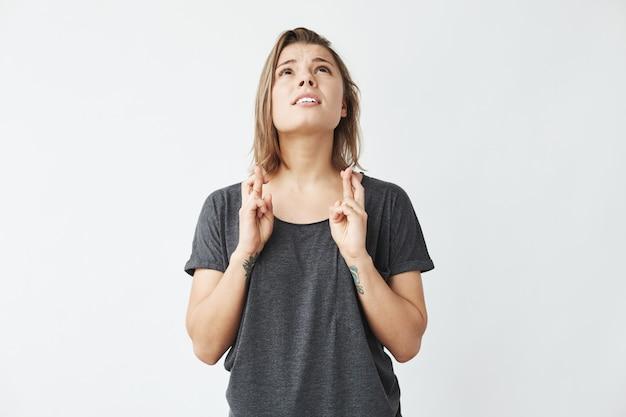 Joven hermosa chica emotiva rezando mirando hacia arriba.