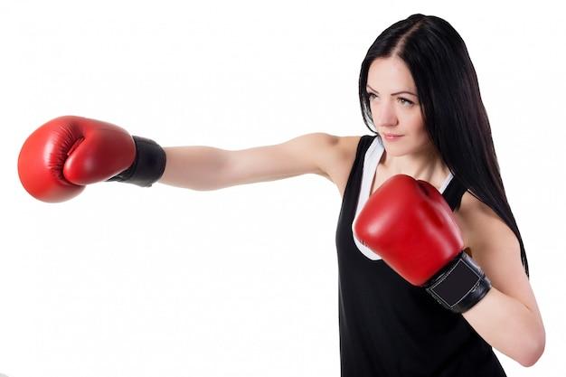 Joven hermosa chica en guantes de boxeo rojos está entrenando una patada