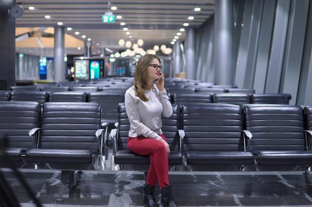 Joven, hermosa chica hablando por teléfono en una terminal de aeropuerto vacía