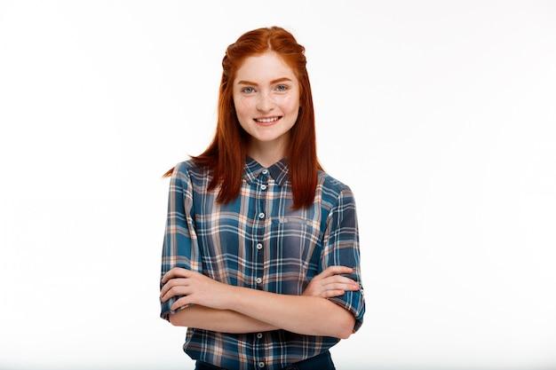 Joven hermosa chica jengibre sobre pared blanca.