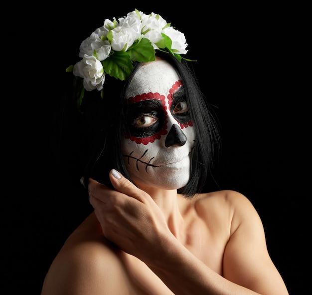 Joven hermosa chica con máscara de muerte tradicional mexicana