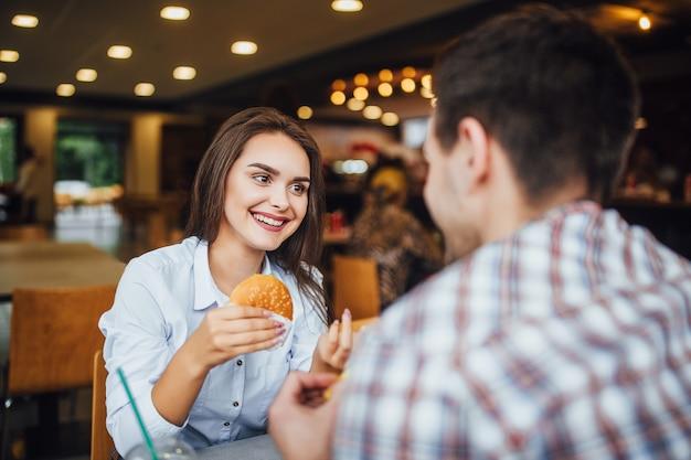 Joven y hermosa chica morena en el almuerzo en un restaurante de comida rápida con un niño comiendo hamburguesas y papas fritas