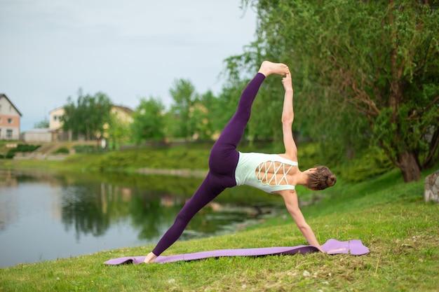 Joven hermosa chica morena caucásica haciendo yoga en un césped verde contra el fondo del río
