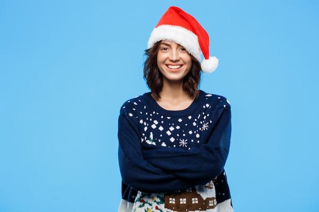 Joven hermosa chica morena en suéter de punto y sombrero de navidad sonriendo sobre pared azul