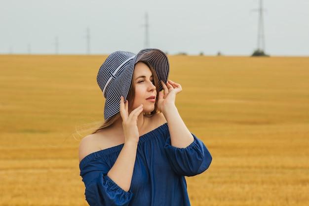 Joven hermosa chica rubia en medio de un campo de trigo ... paisaje de verano, buen clima. vestido de algodón azul, estilo ecológico. hermoso sombrero a rayas.
