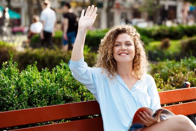 Joven hermosa chica saludo, sentado en el banco en el parque de la ciudad.