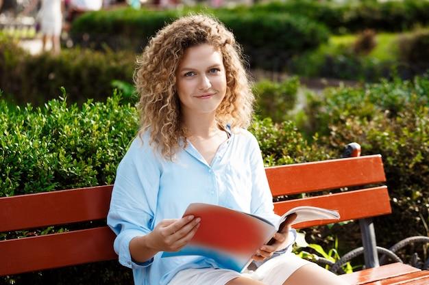 Joven hermosa chica sentada en el banco en el parque de la ciudad.