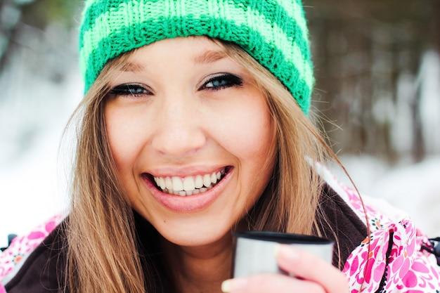 Joven hermosa chica sonriente en una chaqueta carmesí y sombrero verde beber té caliente de un termo en las montañas cubiertas de nieve
