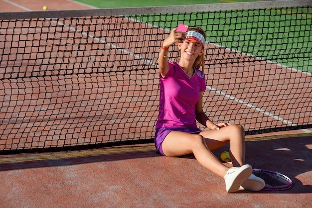 Joven hermosa chica en uniforme rosa y gorra deportiva se sienta en una cancha de tenis cerca de la red y haciendo fotos selfie en teléfonos inteligentes al atardecer. videollamada, comunicación y mensajería mediante teléfono inteligente.