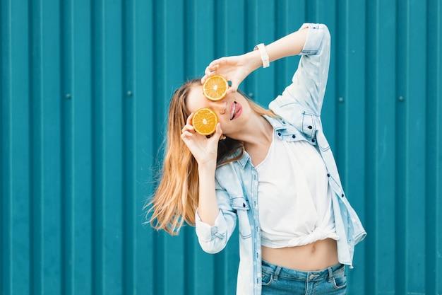 Joven hermosa chica usando dos mitades en naranjas en lugar de gafas sobre sus ojos con la lengua afuera.