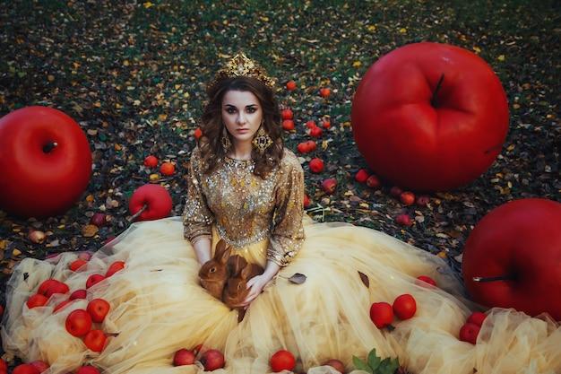Joven hermosa chica en vestido dorado en bosque de otoño