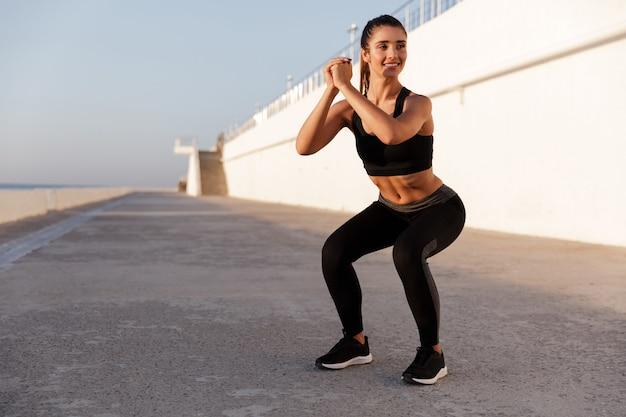 Joven hermosa dama caucásica haciendo ejercicio de abdominales