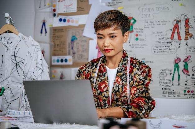 Joven hermosa diseñadora usa computadora portátil para buscar ideas para ropa de diseño