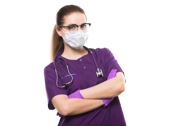 Joven hermosa doctora en máscara médica y guantes estériles con brazos cruzados