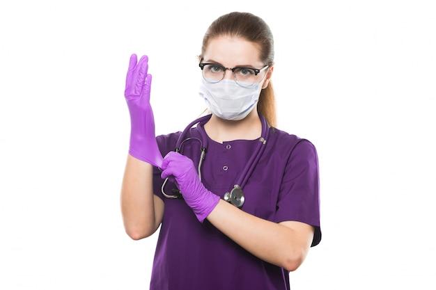 Joven hermosa doctora en máscara médica y guantes estériles