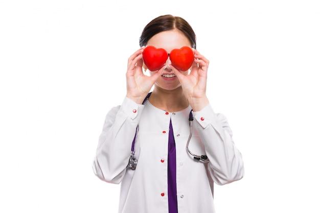 Joven hermosa doctora sosteniendo corazones en sus manos detrás de la cabeza