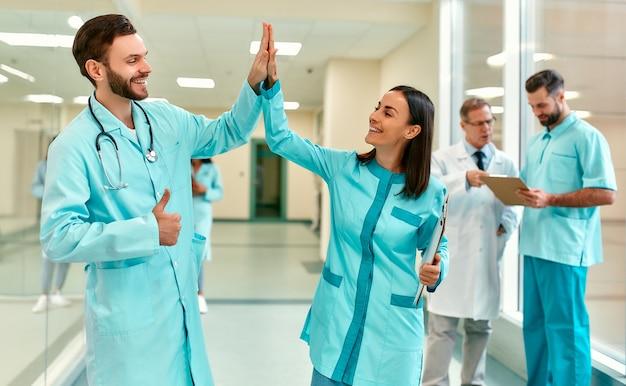Joven hermosa doctora con tarjeta de paciente y un médico con estetoscopio de pie en el pasillo de la clínica