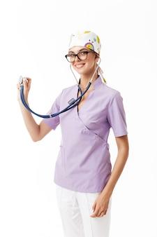 Joven hermosa doctora en uniforme y anteojos usando fonendoscopio soñadora