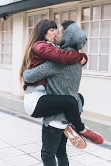 Joven hermosa enamorada pareja abrazándose en medio de la calle de una manera romántica
