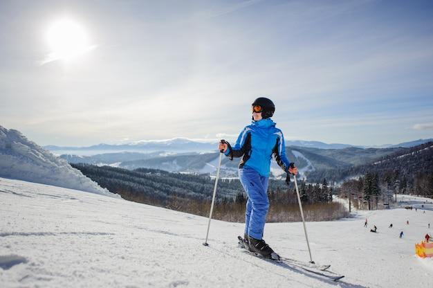 Joven hermosa esquiador femenino en medio de la pista de esquí mirando al sol