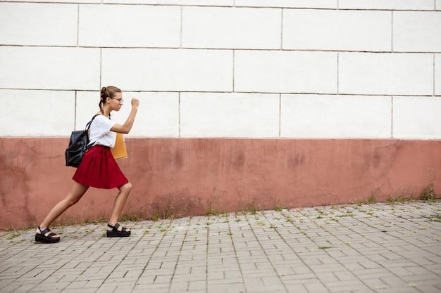 Joven hermosa estudiante en gafas caminando por la calle, sosteniendo carpetas