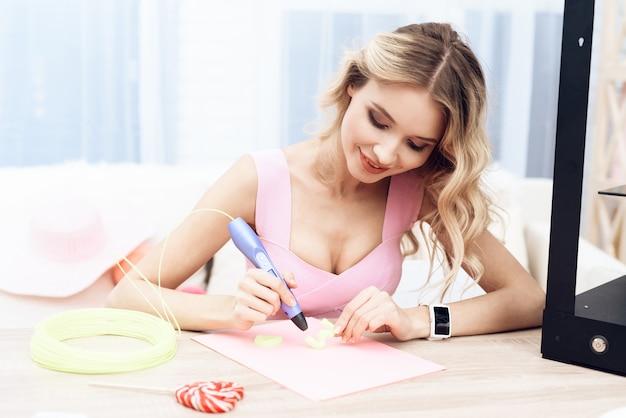 Una joven hermosa está experimentando con un bolígrafo 3d.
