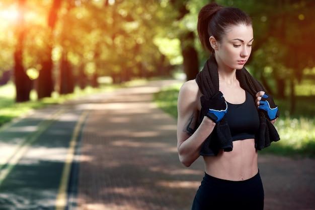Joven hermosa y fuerte mujer descansando después de un entrenamiento activo en el parque de verano. concepto deportivo estilo de vida saludable