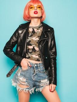 Joven hermosa hipster chica mala en chaqueta de cuero negro y arete en la nariz. mujer despreocupada sexy posando en estudio con peluca rosa cerca de la pared azul. modelo confiado en gafas de sol