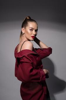 Una joven hermosa con labios rojos y cola alta en un impermeable color borgoña y un sostén negro.