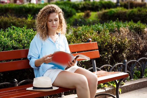 Joven hermosa lectura, sentado en el banco en el parque de la ciudad.
