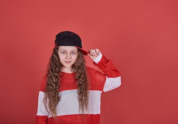 Joven hermosa linda chica bailando en la pared roja, moderna delgada hip-hop estilo adolescente saltando