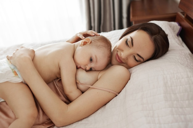 Joven hermosa madre feliz amamantando abrazando a su bebé acostado en cama en casa.