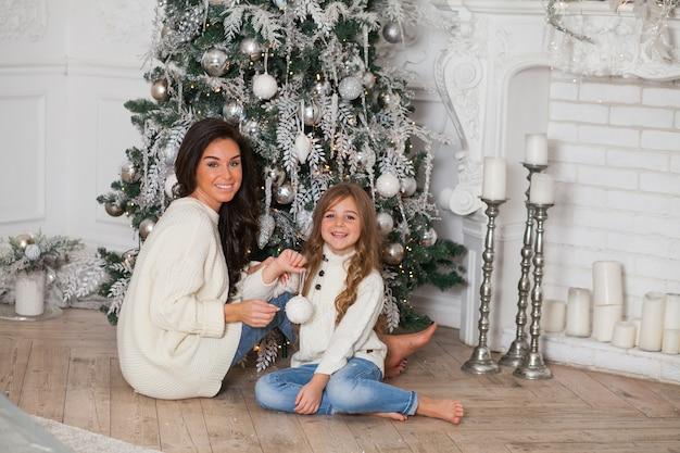 Joven hermosa madre y su pequeña hija linda en suéteres acogedores blancos y una manta se divierten y se abrazan bajo un árbol de navidad decorado. interior clásico hogar festivo.