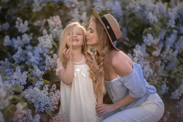 Joven hermosa mamá con cabello largo y rubio camina en el jardín con su hija