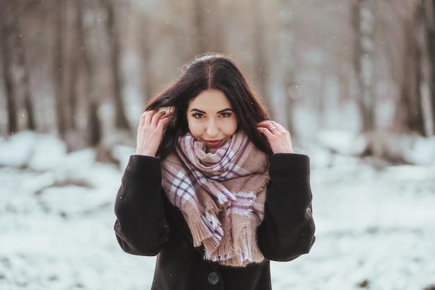 Joven hermosa modelo posando en bosque de invierno